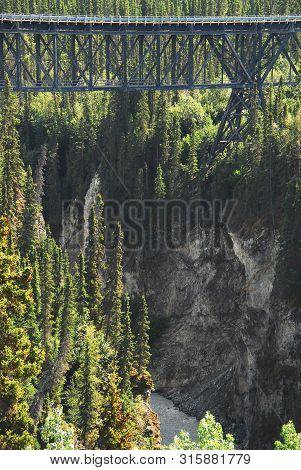 An Old Trestle Railroad Bridge Running Over A Beautiful Deep Gorge Near Wrangell National Park In Al