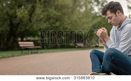 Christian Worship And Praise. A Young Man Is Sitting And Praying In A City Park.