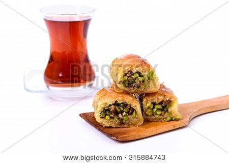 Traditional Turkish Dessert, Baklava On The Wooden Plate With Pistachio Nuts And Turkish Tea With Sp