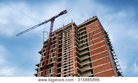 Construction Site Background. High-rise Red Brick Building Under Construction. Crane Near The Buildi