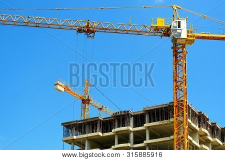 Two Tower Cranes And Building Activity. Construction Site Background. Industrial Background.
