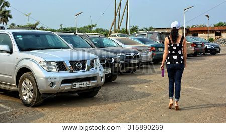 Nice Woman Goes Along A Row Of Beautiful Cars At A Parking Lot In A Sunny Day. Vehicles. Ghana, Accr