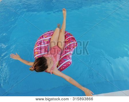 Young Beautiful Girl Relaxing And Swimming In The Blue Swimming Pool With A Pink Circle Closeup.