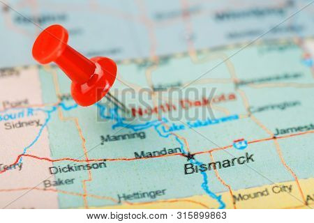 Red Clerical Needle On A Map Of Usa, North Dakota And The Capital Bismarck. Closeup Map North Dakota
