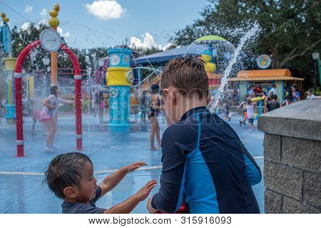 Orlando, Florida. July 30, 2019. Nice Kid And Little Boy Playing With The Water Jet In Sesame Street