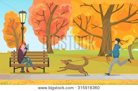 Autumn Park, Man Running With Dog Near Woman Talking By Phone On Bench Under Streetlight. Fall Leave