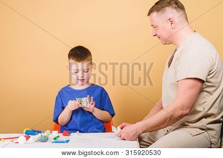 Kid Little Doctor Sit Table Medical Tools. Health Care. Medical Examination. Salary Of Hospital Work