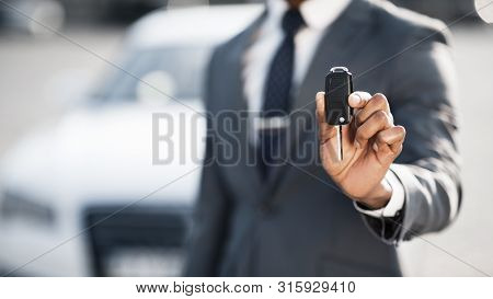 New Car Owner. Businessman Showing Car Key Against Luxury Auto, Copy Space