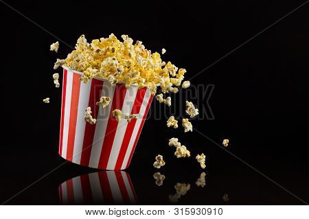 Flying Popcorn From Striped Bucket Isolated On Black Background