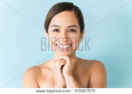 Closeup Of Smiling Flawless Woman With Bare Shoulder Over Blue Background