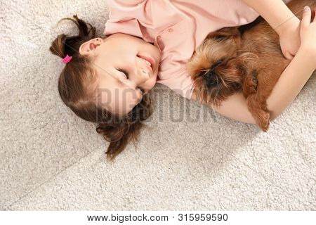 Portrait of cute girl with funny Brussels Griffon dog lying on carpet, above view. Loyal friends poster