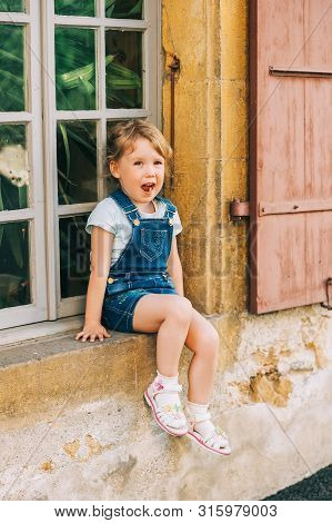 Outdoor Portrait Of Cute Little 3-4 Year Old Girl, Wearing Denim Pinafore, Sitting By The Window