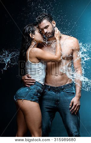 Sexy And Wet Woman Hugging Handsome And Muscular Boyfriend Under Raindrops On Black