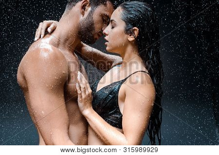 Attractive Woman Hugging Shirtless And Wet Man Under Raindrops On Black