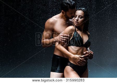 Shirtless Man Hugging Sexy And Wet Girl Under Raindrops On Black