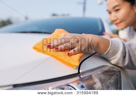 A woman cleaning car with microfiber cloth, car detailing (or valeting) concept poster