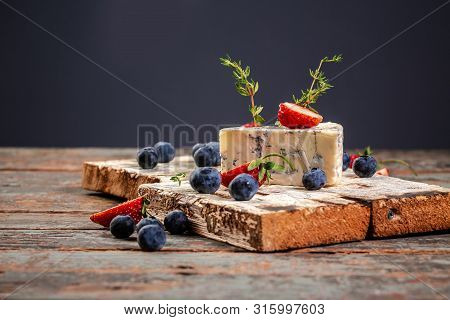 Roquefort, French Blue Cheese With Mold On A Wooden Surface, Served With Blueberry And Strawberry.