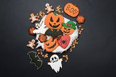 The hand-made eatable gingerbread Halloween pumpkin, ghosts, bat and sceletons on black background poster