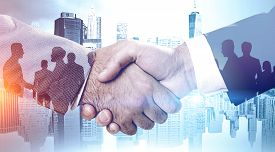 Close Up Of Two Businessmen Shaking Hands In Modern City With Double Exposure Of Business People Sil