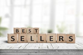 Best Sellers Sign On A Wooden Desk In A Bright Room With Green Plants