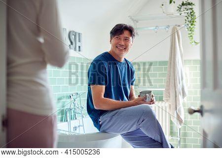 Mature Asian Couple Wearing Pyjamas Sitting In Bathroom Enjoying Morning Hot Drinks Together