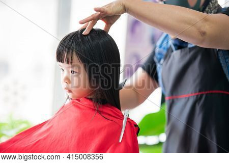 Adorable Black Haired Asian Girl Being Styled In Hairdressing Salon By A Female Hairdresser With A F