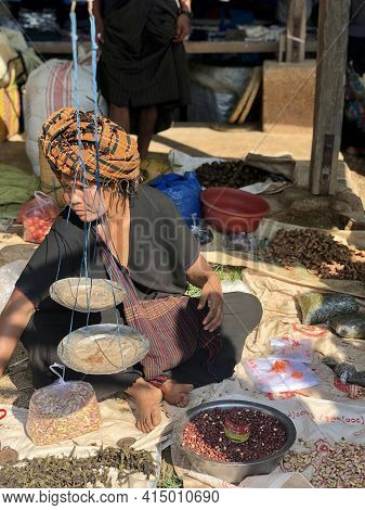 Inle Lake, Myanmar - November 9, 2019: Pao Tribe Woman Weighing Beans For Sale In In Dein Five-day M