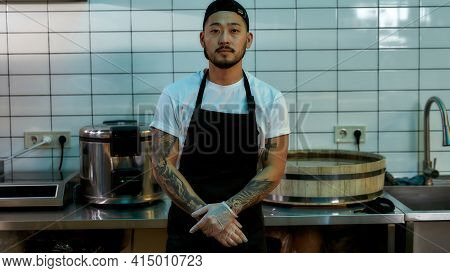 Middle Aged Asian Chef In Kitchen Gloves. Cook In Uniform Standing In The Cuisine. Bearded Man With
