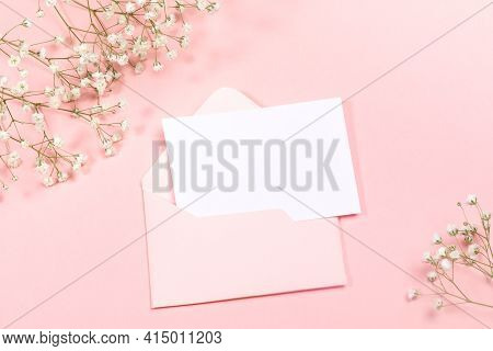 Pastel Pink Festive Layout With Envelope, Empty Sheet, White Gypsophila Flowers. Copy Space For Text