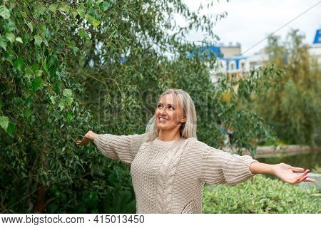 Beautiful Young Blonde Woman In White Sweater, Smiling, Laughing And Looking At Sky. Hands Are Raise