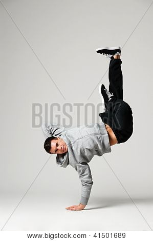 studio shot of breakdancer posing over grey background
