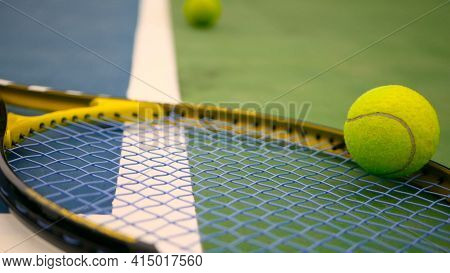 Close Up Of Tennis Equipment On The Court. Sport, Recreation Concept. Yellow Racket With A Tennis Ba