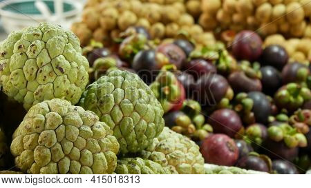 Assorted Exotic Fruits On Stall In Market. Bunch Of Sugar Apples Placed On Blurred Background Of Lon