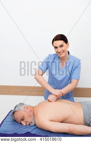 Masseuse Smiling At Camera While Doing Back Massage To Man In Rehabilitation Center.