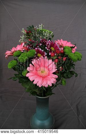 Bouquet Of Fresh Mixed Colorful Flowers In Elegantly Shaped Clay Vase Isolated On Grey Cloth Backgro