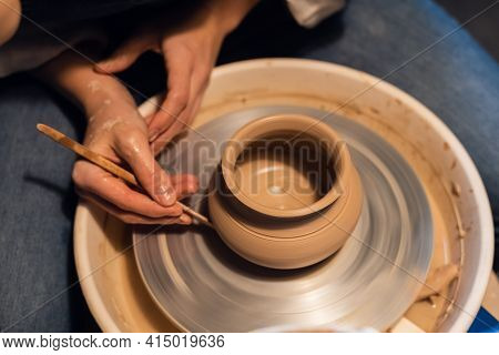 A Potter Girl Sculpts A Pot On A Potters Wheel With Her Hands And Tools.
