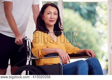 Portrait Of Asian Woman In Wheelchair Being Pushed By Carer At Home