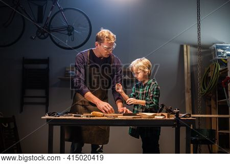 A Young Father Teaches The Basics Of Carpentry To His Son In The Garage.
