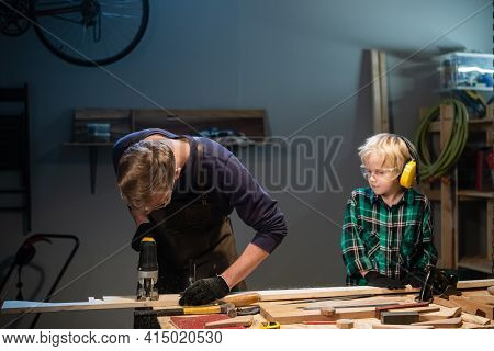 An Experienced Carpenter And His Young Apprentice Make Wood Crafts In Their Workshop.