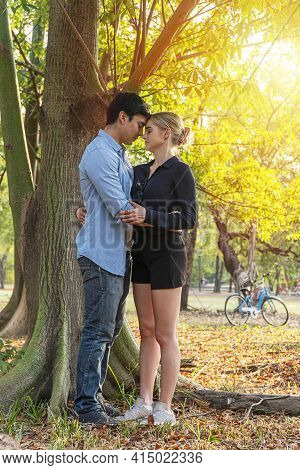 Romantic Young Couple Standing Under Big Tree While Embracing On Sunset In The Park. Cheerful Man Hu