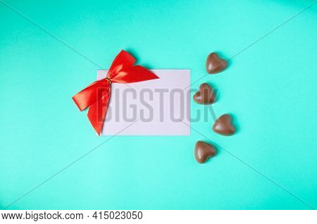Chocolate Hearts On A Turquoise Background, Close-up. International Chocolate Day, Postcard, Concept