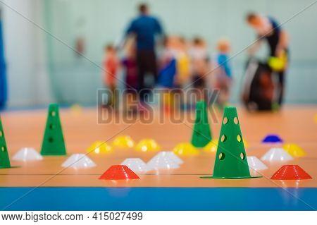 Group Of School Sports Equipment On Wooden Floor. School Children Training Soccer At Indoor Soccer F