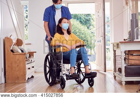 Mature Asian Man Wearing Face Mask Pushing Wife In Wheelchair At Home During Health Pandemic