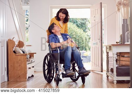 Asian Woman Pushing Husband In Wheelchair At Home Back From Shopping Trip With Bag