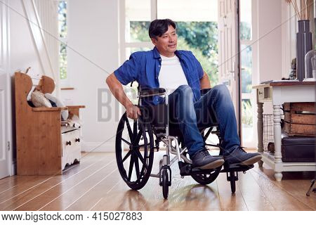 Mature Asian Man In Wheelchair Pushing Himself Along Hallway At Home