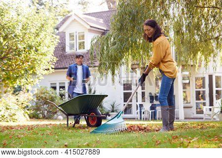 Mature Asian Man Bringing Hot Drink To Woman Tidying Garden With Rake