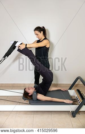 A Woman Practicing Exercises With A Pilates Personal Trainer On Reformer.