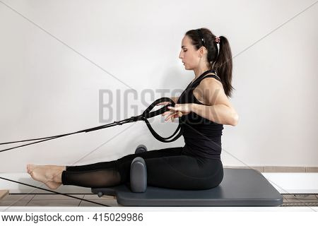 A Woman Doing Pilates Exercises Pulling Elastic Bands On A Reformed Bed.