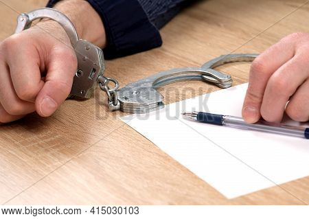 A Detainee At The Police Station. One Hand Is Cuffed, The Other Is Unbuttoned, And There Is A Pen In