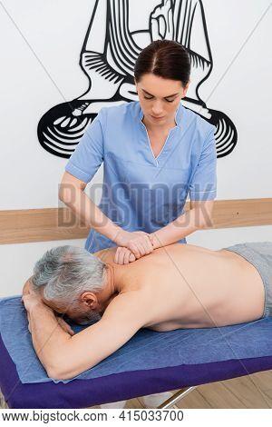Brunette Masseuse Doing Back Massage To Mature Man.
